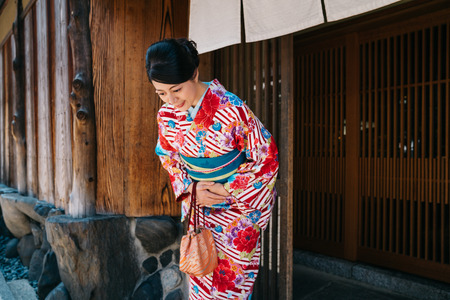 Japanese lady bowing in front of her house with beautiful kimono. traditional lifestyle in jp. attractive woman with colorful kimono clothing in summer. Imagens