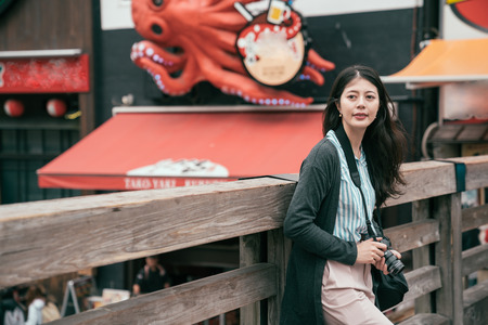 cheerful lady traveler relaxing on the wooden bridge. young backpacker sightseeing in osaka on holidays. Traveling tour osaka attractions in Asia concept.