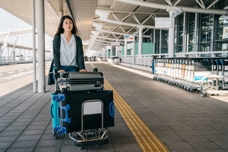 businesswoman walking fast through the luggage cart and rolling car. young lady going to work abroad visiting clients. elegant woman outside international airport with trolley in sunny day. Stok Fotoğraf - 115081903