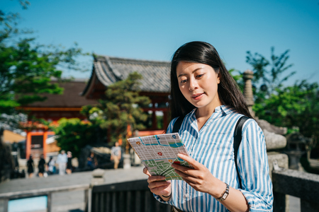 tourist holding the map standing in Japanese temple and considering the route to the next spot. young asian woman travel in summer vacation on sunny day. Traveling tour in Asia.