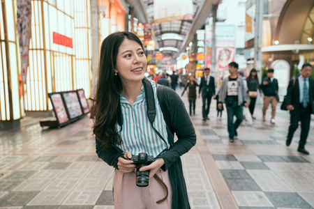 woman enjoy the view of the shopping center and holding camera ready to photograph. young traveler walking in the indoor street. happy tourist having fun on summer travel jp.