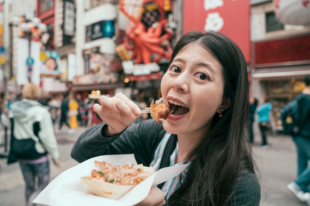young lady traveler eating takoyaki on the teeming street. girl tourist trying tasty japanese octopus balls on the famous street dotonbori. self-guided trip in japan concept. Stock fotó
