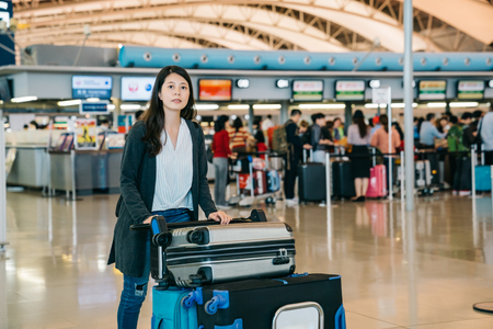 asian woman walking through airport counter going to terminal pushing cart with carry-on hand luggage for flight travel. people lining up in the background waiting to check in. young lady worker.