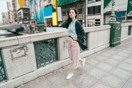 full length photo of young office lady walking on the bridge. japanese businesswoman in smart casual busy going to work in morning. pretty girl lifestyle in japan. Stock Photo