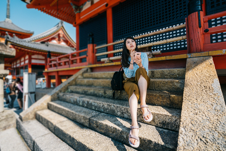 traveler sitting on the stairs relaxing after visited the temple and thinking the next sightseeing spot. young tourist using online guide app to experience Kyoto Japan. young girl self trip concept.