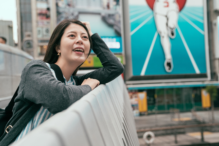 elegant female traveler relying on the bridge next to the billboard. famous attraction in osaka nippon runner. enjoy travel in japan.