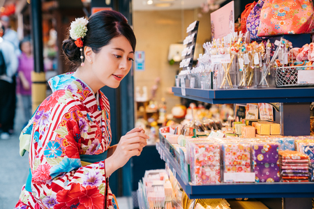 Japanese young girl wearing kimono and choosing handkerchief in the shop. pretty lady with traditional dress shopping in the vendor. Japanese teenager lifestyle.