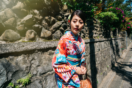 Japanese lady with traditional dress relaxing relying on the stone wall and waiting for someone. young girl first time wearing ladies kimono in Kyoto. patient woman standing on sunny day in jp.