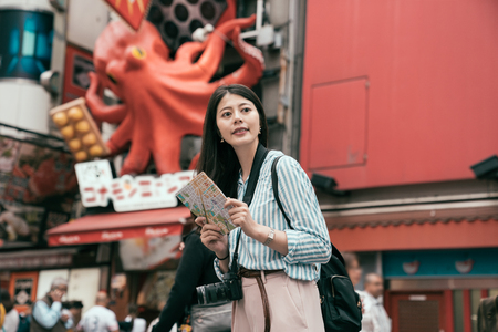 lady traveler holding map standing on the busy street on the dotonbori. female lady photographer travel in osaka. happy female tourist searching road to hotel in a foreign city during vacation.
