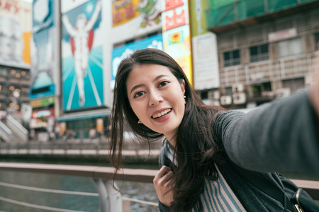 lady traveler using cellphone taking selfie with runner sign in osaka. famous osaka attraction in japan. woman taking self portrait while walking by the canal.