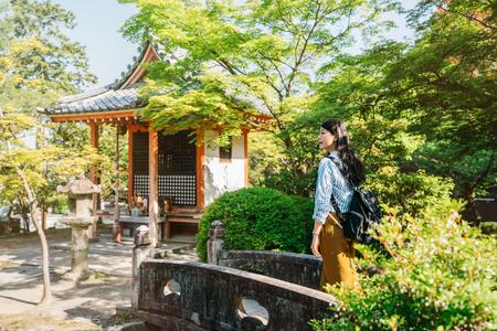 elegant female traveler walking on the little bridge to the quiet green garden. young girl having japan tourism in summer holidays. Enjoying sunlight in Otowa san. Stock Photo