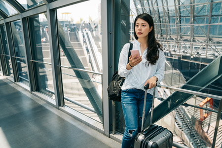 elegant asian office lady holding cell phone and luggage standing on the corridor. young business woman going abroad for business trip visit customer. Morning commute to work or travel.