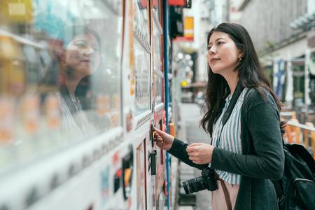Japanse automaat. Jonge vrouwelijke toerist die een hapje of een drankje kiest bij de automaat. dame die munten in de verkopersmachine op de japanse straat stopt. Stockfoto