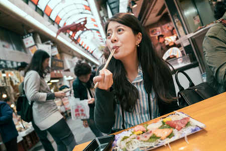 beautiful tourist enjoying sashimi by chopsticks. traveling girl excited eating fresh raw fish in vendor. young traveler sitting in the vendor in indoor market.