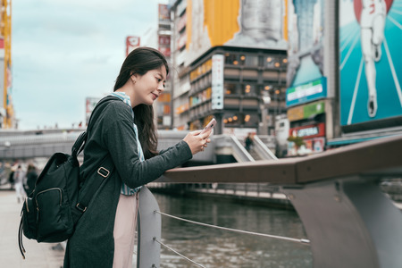 lady traveler using cellphone texting sms message. young backpacker relying next to the canal in osaka. beautiful tourist on mobile phone chatting beside river. Stock Photo