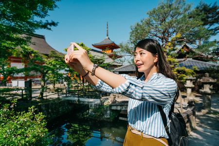 female tourist taking picture of the beautiful view in the garden in Japanese temple. young traveler taking selfie at phone with green pond. Buddhist pagoda standing in the background on sunny day. Banco de Imagens