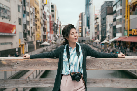 lady tourist visiting japan relaxing relying on the wooden bridge. wind blowing asian girl black long hair in spring. young traveler enjoying japan trip. Stock Photo