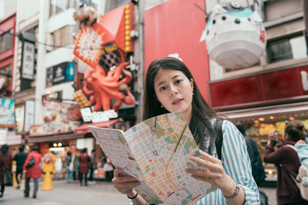 young lady traveler holding map on the dotonbori. cute tourist finding right direction on the teeming street in osaka. female traveler trip in japan asia.