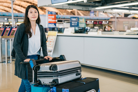 young female traveler pushing cart leaving walking to the gate after checked in. busy counter in the kix airport. attractive tourist finished travel in japan lifestyle concept.