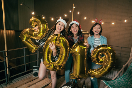 asian ladies enjoy music on balcony celebrating new year eve outdoor. young girls showing 2019 balloons on the roof at night. group of best friends enjoy party lifestyle concept. Stock Photo - 111846502