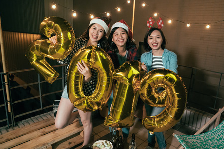 young girls showing 2019 balloons on the roof at night party. friends with christmas hats cheerfully having fun smiling outdoor. fashion asian ladies ecited for coming up new year. Stock Photo