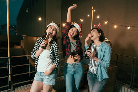 young girls dancing dark night christmas party outdoor. cheerful ladies with alcohols beers enjoy music on balcony. Carefree girlfriends on rooftop terrace lifestyle concept.