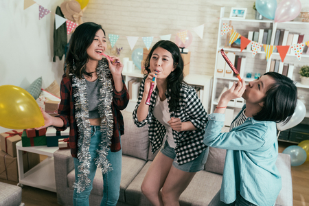 young girls having fun with blowers in cozy room in house full of colorful confetti. attractive asian female with yellow balloon funny blowing the toy. celebrating party at home lifestyle concept.