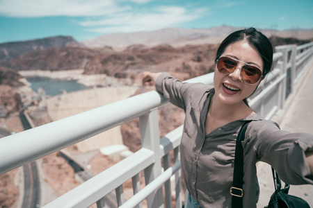 young asian girl traveler with sunglasses taking selfie pointing finger to the pond in nature. elegant tourist happy trip on sunny day in hoover dam visit in usa. teenager having fun outdoors. Stock Photo