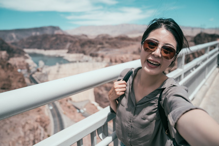 young asian traveler with sunglasses taking self portrait in hoover dam visit. elegant tourist happy travel in sunny nature in usa. pretty girl smiling face to camera selfie.