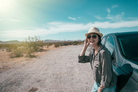 female car driver standing on the empty nature sunny day relying on the black car. young woman with straw hat and sunglasses enjoy the beauty of the wild during the trip. asian lady self driving tour Banque d'images