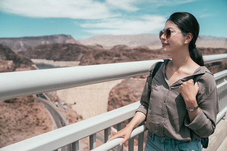 young female backpacker wearing sunglasses sightseeing the nature desert. elegant traveler standing high holding the handrail with joyful face looking at the scenery of hoover dam in nevada.
