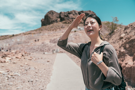 Cheerful traveler standing in the desert finding hoover dam in nevada. young asian tourist hands cover the sunlight to face in a sunny day. attractive woman traveling alone in america lifestyle.