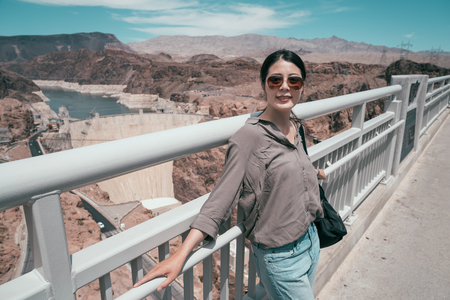 young girl traveler relying on the handrail with amazing nature view in the background. Joyful lady tourist standing outside hoover dam visitor center. trip outdoor on sunny day.