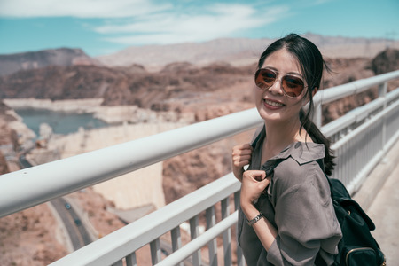 young girl tourist carrying heavy backpack turn over face to camera smiling. asian traveler with sunglasses seeing hoover dam location. Travel summer holiday girl enjoying wild nature. Stock Photo