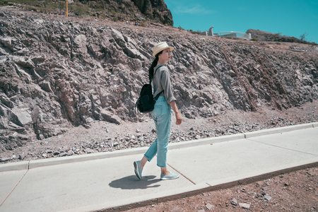 full length of elegant traveler wearing hat walking in mountain on sunny day. young asian tourist carrying bag visiting the desert. Joyful lady hoover dam tours on holidays.