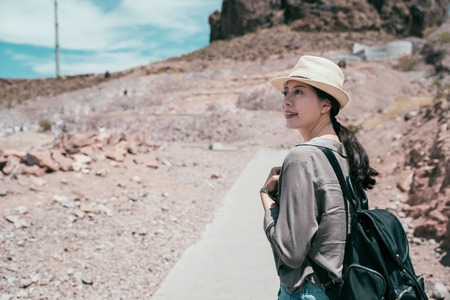 Cheerful traveler in straw hat visit hoover dam. young wild tourist love nature adventure. female backpacker joyfully travel in usa in summer. Stock Photo