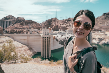 young girl traveler pointing finger to the building during the hoover dam tours. lady tourist with sunglasses smile confidently to the camera. joyful lady happy self trip in usa.