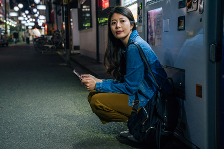 japanese woman crouch down by the vending machine waiting for friend. elegant lady using cellphone contact app outdoor at night in the city. traveler online map finding the way to hotel in osaka.