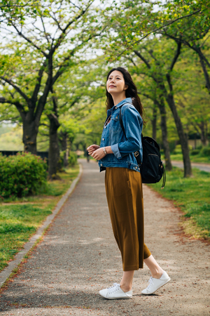 full length of cheerful traveler standing in the path looking up to the sky. elegant woman enjoy the beauty of the green park in summer. asian girl tourist travel in osaka lifestyle concept. Reklamní fotografie - 112052321