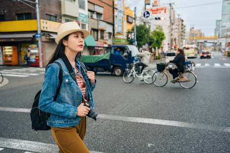 young happy woman walking on the road in osaka japan. beautiful tourist woman visiting the city with camera. busy street with truck driving through and bicycle riding pass. Banco de Imagens