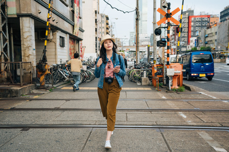 full length of young girl traveler walking pass cross the railway. elegant lady tourist backpacker trip in osaka japan alone. woman curious seeing city. 免版税图像