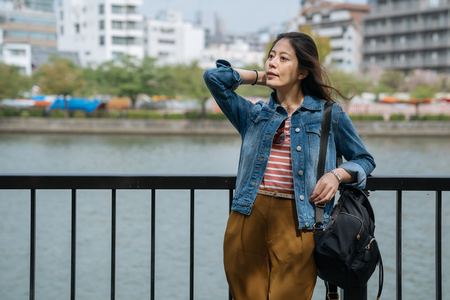 japanese woman relaxing near the clean river with winds blowing hair on holiday. young office lady rest relying on handrail after work enjoying beautiful city view. local people lifestyle.