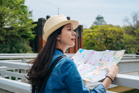 young elegant woman tourist holding a paper map and searching the right way. green trees surrounding female traveler with straw hat. relaxing backpacker visiting osaka japan alone independent trip.