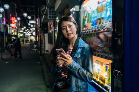 japanese woman relying on japan vending machines using cellphone relaxing. Young student or female tourist with camera texting sms by phone standing by the auto vendor. girl outdoor at night osaka jp Stock Photo