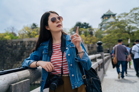 young woman tourist with sunglasses visit japan castle and relaxing pointing finger to blue sky. many people walking to osaka tower. female lens man standing relying on handrail carrying camera.