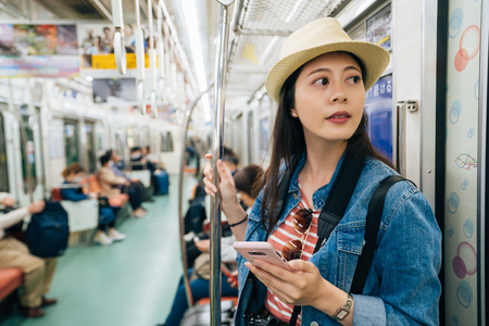 young travel woman using cellphone inside train compartment. elegant girl tourist looking outside the window. asian lady self-guided trip in osaka japan concept.