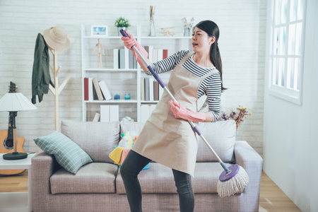 female housekeeper wearing apron dancing with mop while doing housework. young asian wife playing singing doing house chores in the living room enjoy the music. happy woman having fun at home.