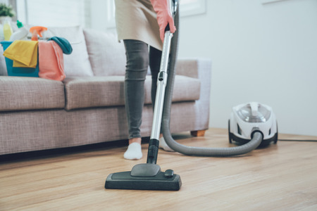 asian woman using vacuum cleaner in the living room. housekeeper wearing pink protective rubber gloves cleaning the wooden floor in the house. full of clean supplies in bucket on comfortable sofa Foto de archivo - 112722628