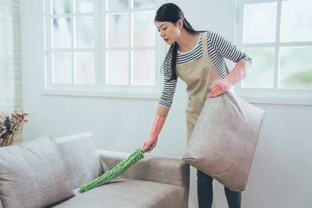 elegant wife in rubber protective gloves using feather duster cleaning the couch. young housewife dusting sofa holding up the pillow in bright living room standing next to the window. Archivio Fotografico