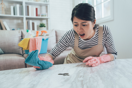 asian housewife with a shock frowning face cleaning the marble table with dirt on it. lady unsatisfied opening mouth doing housework at home. woman in apron and protective gloves using rag wiping. 写真素材